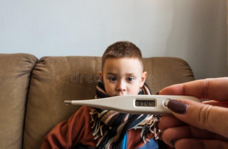 Młoda chłopiec jest ubranym pulower i szalika obsiadanie na kanapie, podczas gdy jego matka sprawdza jego temperaturę z pomocą te zdjęcia royalty free