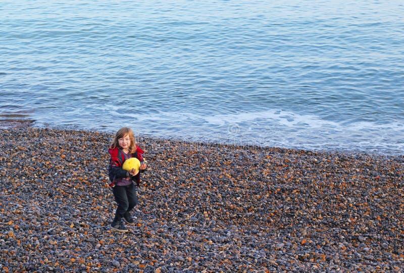 Młoda chłopiec na otoczak plaży zdjęcie royalty free