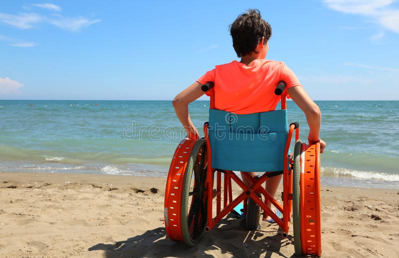 Młoda chłopiec na wózku inwalidzkim na plaży zdjęcie royalty free