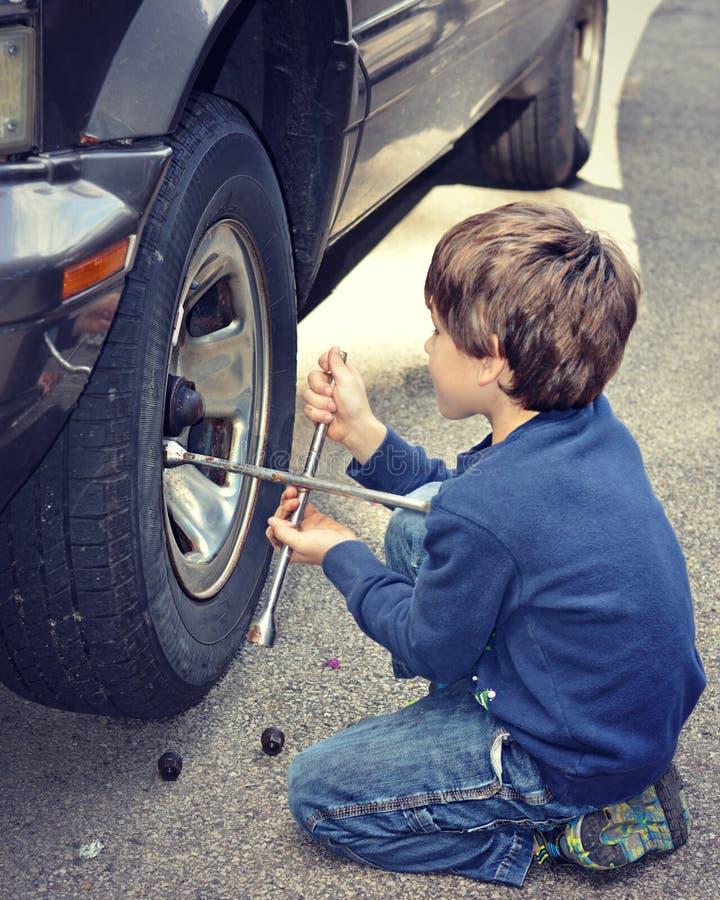 Młoda chłopiec odmieniania opona zdjęcia stock