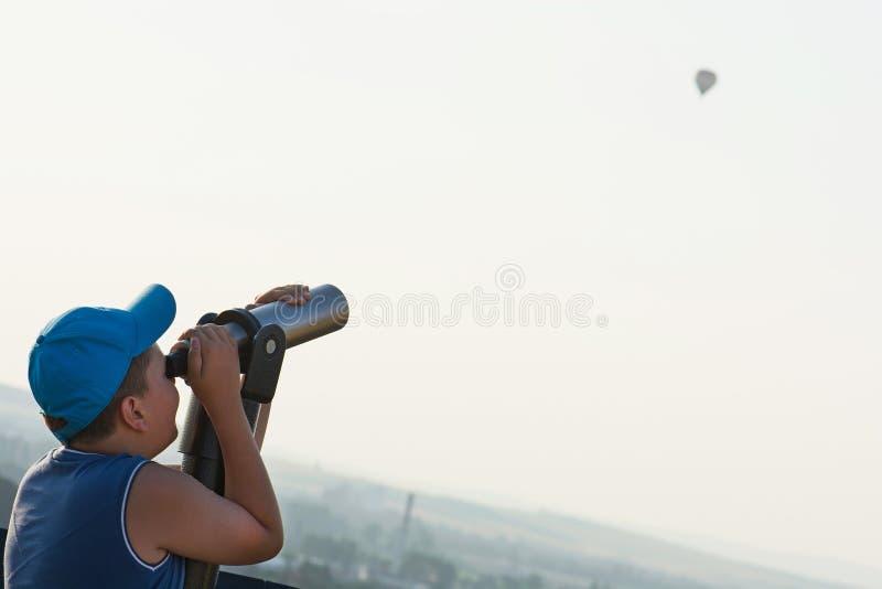 Młoda chłopiec ogląda latającego baloon przez teleskopu fotografia stock