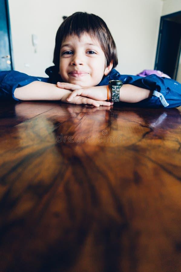 Młoda chłopiec opiera na stole obrazy royalty free