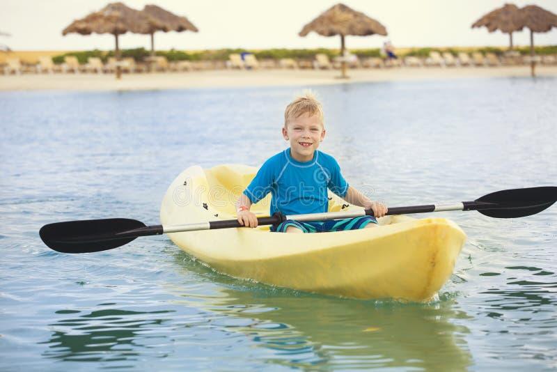 Młoda chłopiec paddling kajaka przy plażą na wakacje zdjęcie stock