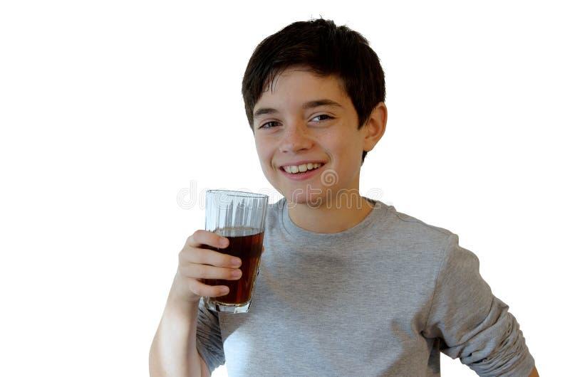 Młoda chłopiec pije i ono uśmiecha się zdjęcie stock