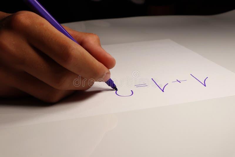 Młoda chłopiec pisze szczególnej liczbie na papierze On calcute niektóre arytmetyczny problem przy szkołą fotografia royalty free