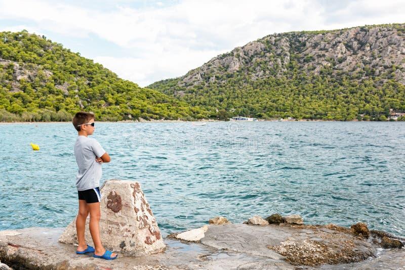 Młoda chłopiec podziwia seascape Malowniczy miejsca Grecja zdjęcia royalty free