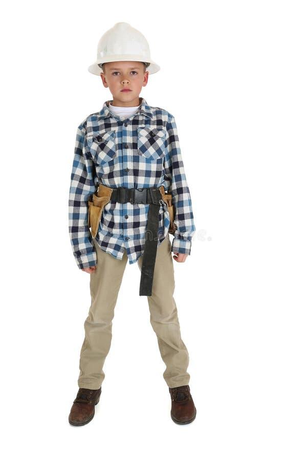 Młoda chłopiec pozycja jest ubranym budowy hardhat zdjęcie royalty free