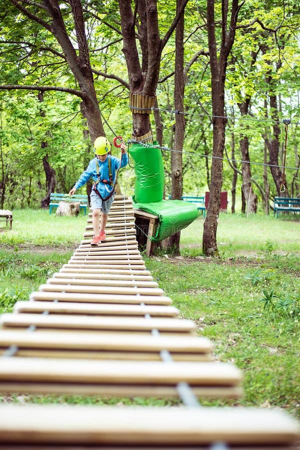 Młoda chłopiec przechodzi kablową trasę wśród drzew, krańcowy sport w przygoda parku obrazy royalty free