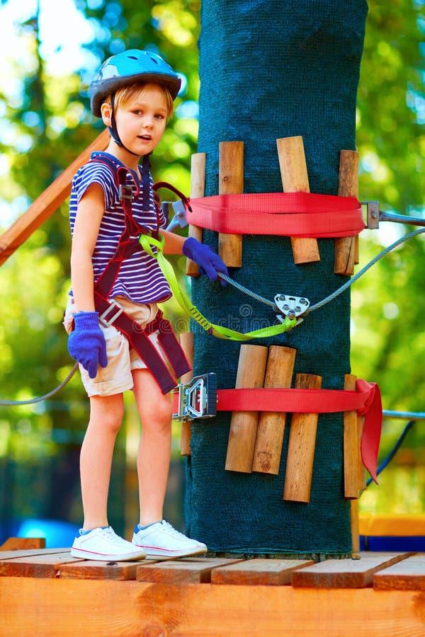 Młoda chłopiec przechodzi kablową trasę wśród drzew wysoko, krańcowy sport w przygoda parku obraz stock
