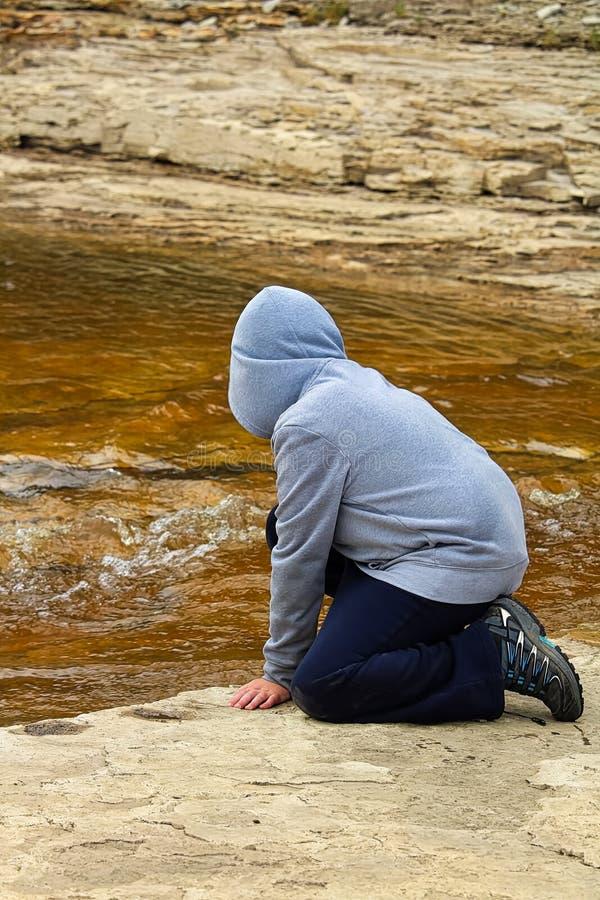 Młoda chłopiec przy rzeki krawędzi dopatrywania wody spływaniem zdjęcie stock