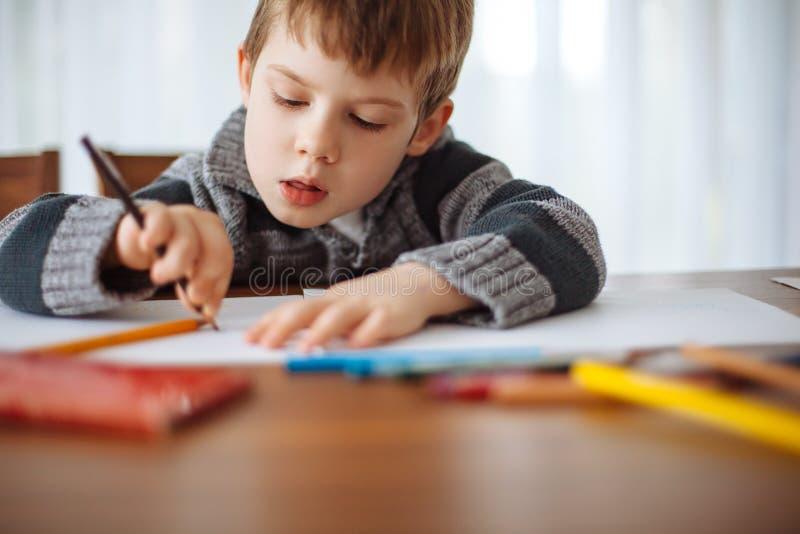 Młoda chłopiec rysuje w domu obrazy stock