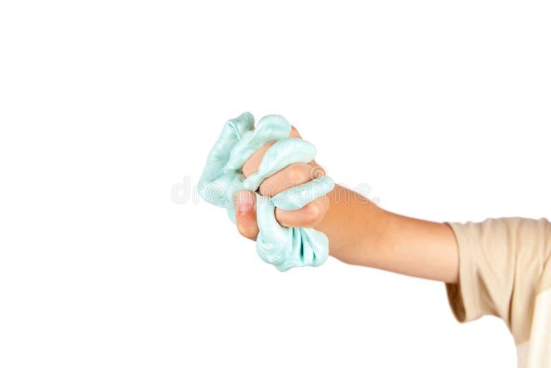 Młoda chłopiec ` s ręka gniesie błękitnego śluzowacieje zabawkę fotografia stock