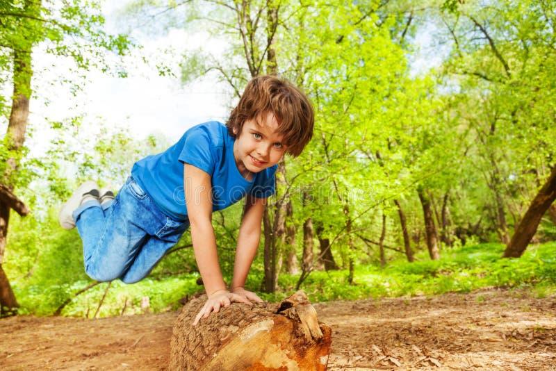 Młoda chłopiec skacze nad nazwy użytkownika lata lasem zdjęcie royalty free