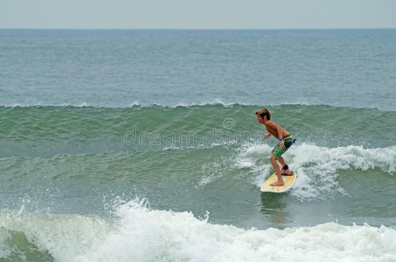 Młoda chłopiec Surfuje Wrightsville Plażowego, NC obrazy stock
