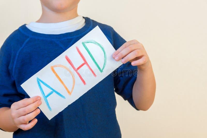 Młoda chłopiec trzyma ADHD tekst zdjęcie royalty free