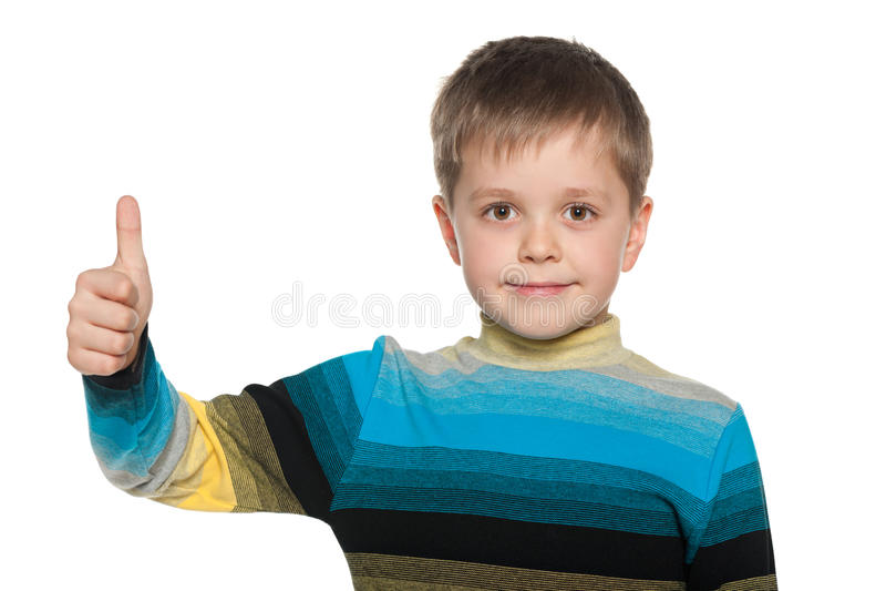 Młoda chłopiec trzyma jego kciuk up obraz royalty free
