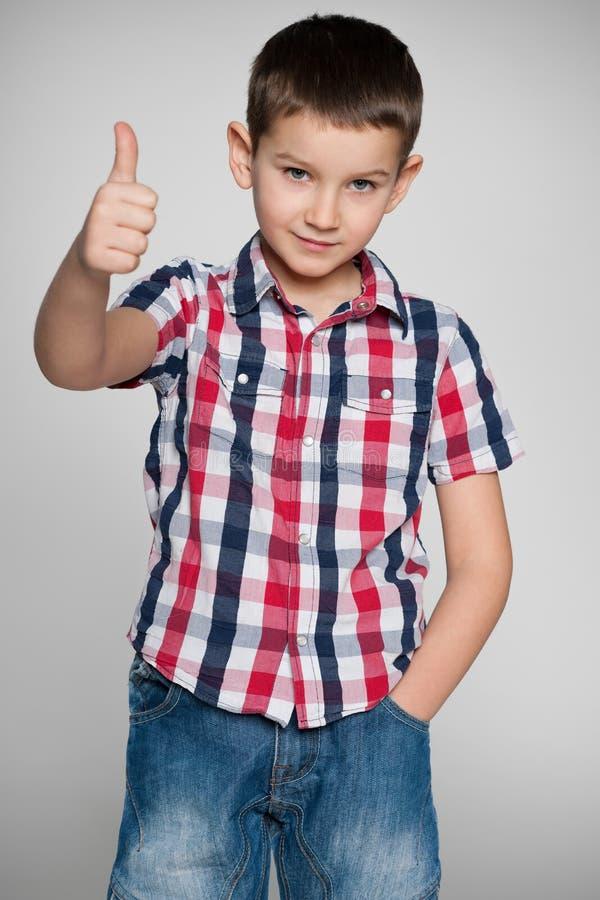 Młoda chłopiec trzyma jego kciuk up na popielatym tle zdjęcia royalty free
