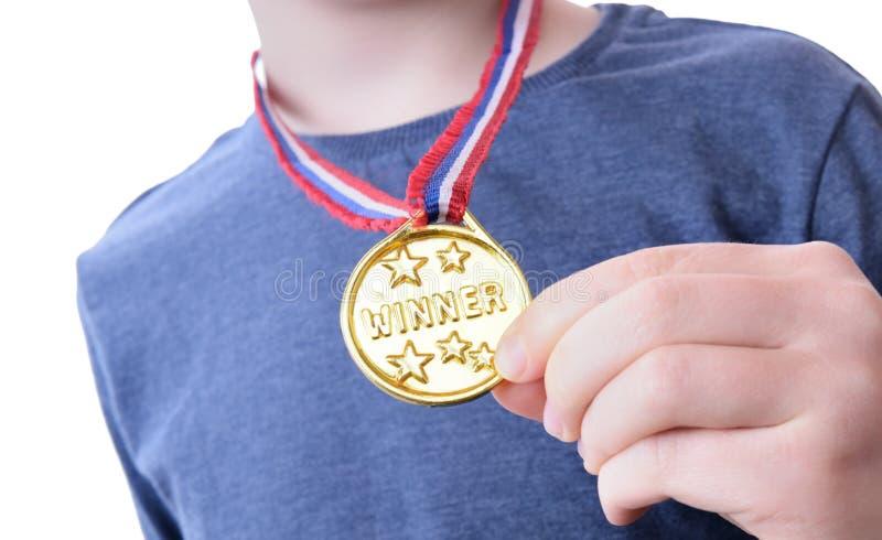 Młoda chłopiec trzyma up jego zwycięzca odznakę fotografia royalty free