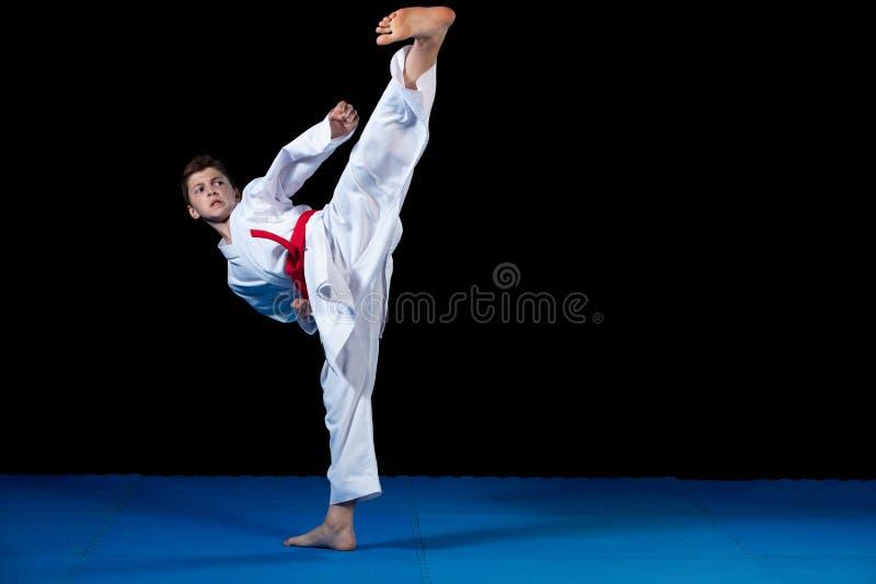 Młoda chłopiec ubierał w białym karate kimonie z czerwień paskiem zdjęcie royalty free