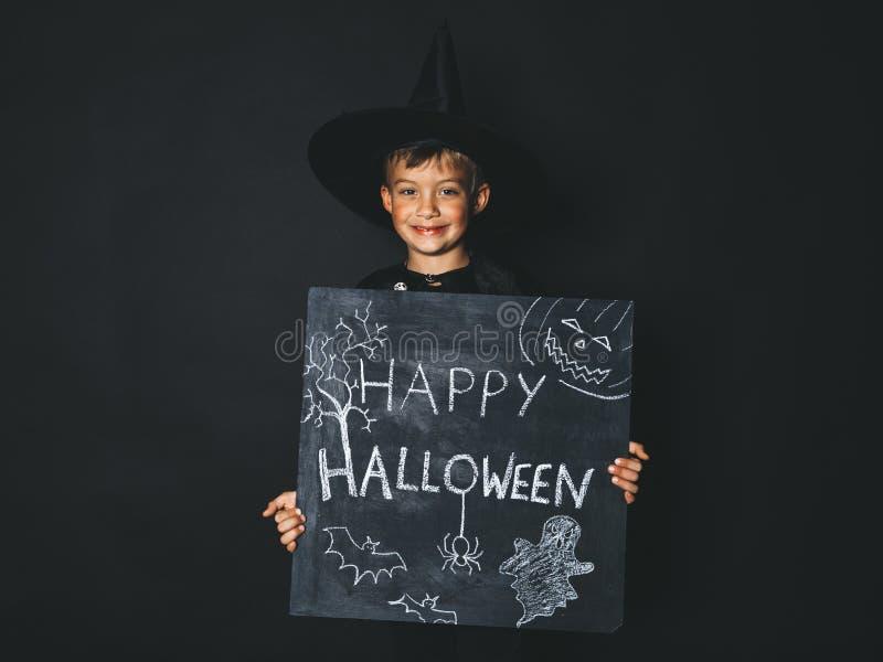 Młoda chłopiec ubierająca jako magik trzyma szczęśliwego Halloween chalkboard zdjęcia stock