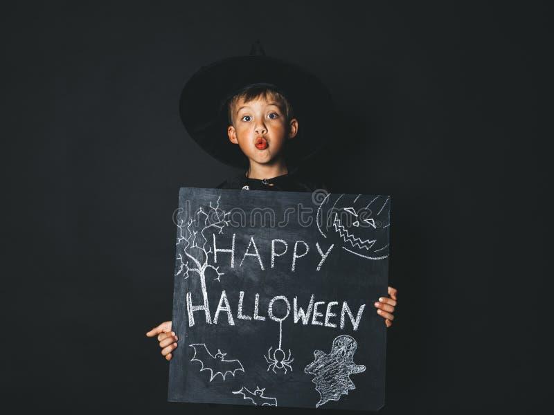 Młoda chłopiec ubierająca jako magik trzyma szczęśliwego Halloween chalkboard fotografia stock