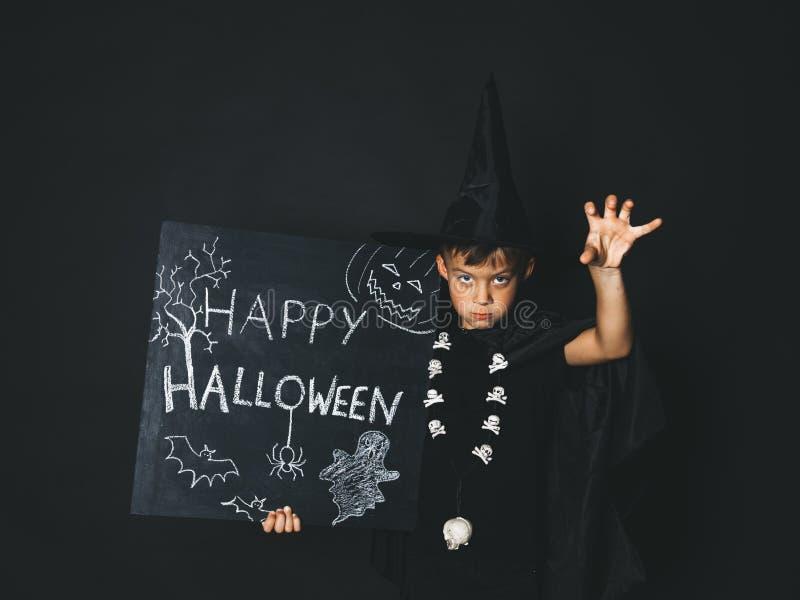 Młoda chłopiec ubierająca jako magik trzyma szczęśliwego Halloween chalkboard obraz stock