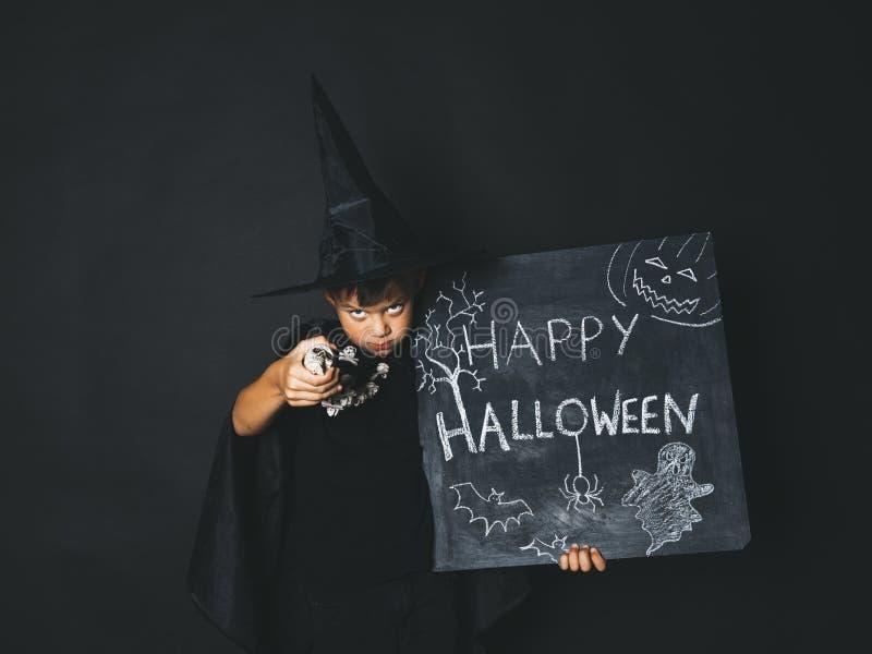 Młoda chłopiec ubierająca jako magik trzyma szczęśliwego Halloween chalkboard zdjęcie royalty free