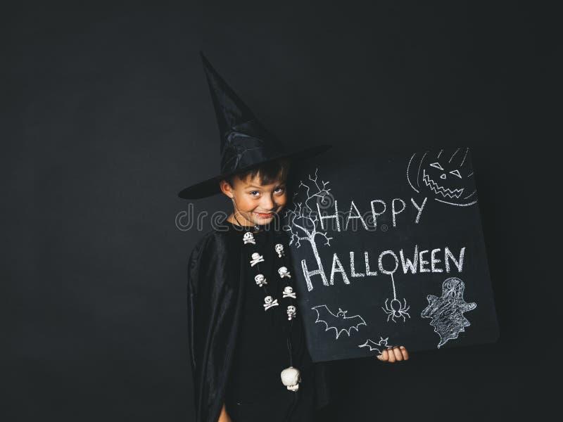 Młoda chłopiec ubierająca jako magik trzyma szczęśliwego Halloween chalkboard obraz royalty free