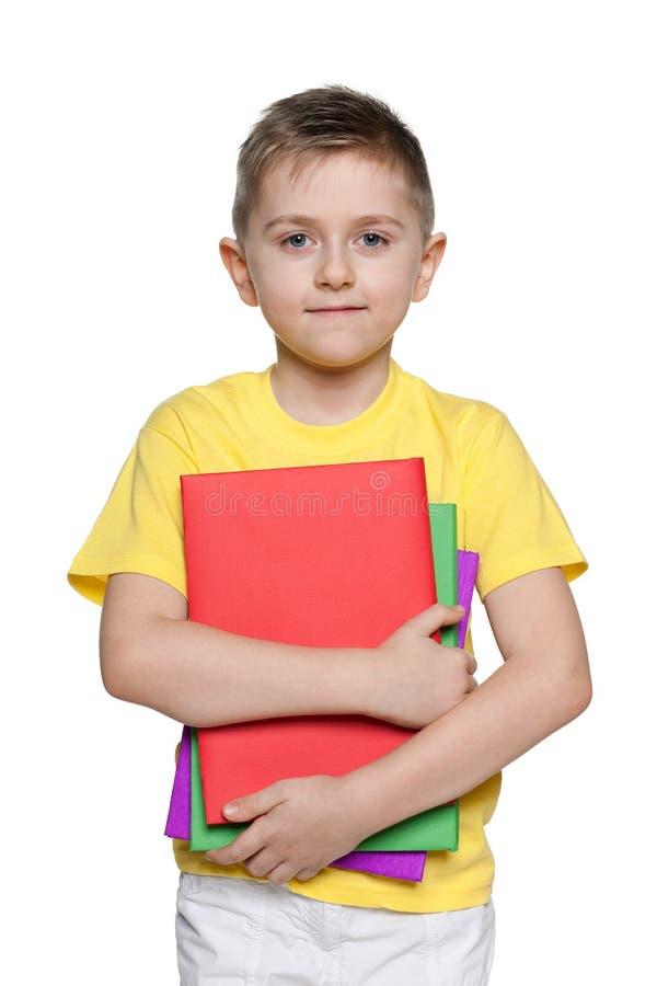 Młoda chłopiec w żółtej koszula z książkami zdjęcie royalty free