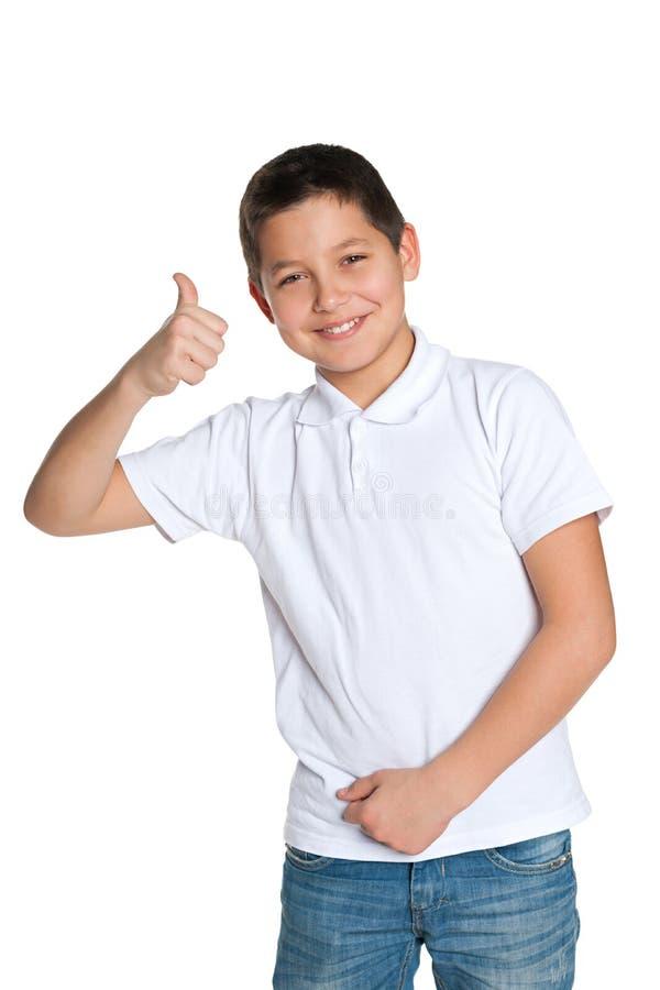 Młoda chłopiec w białej koszula trzyma jego kciuk up zdjęcia royalty free