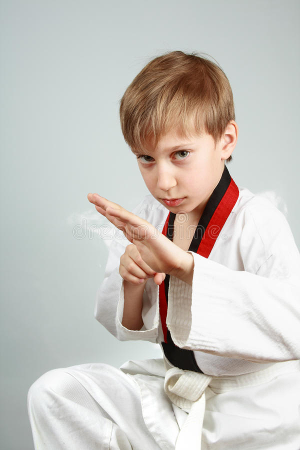 Młoda chłopiec w karate kostiumu ćwiczy sztukach samoobrony patrzeje groźny obraz stock