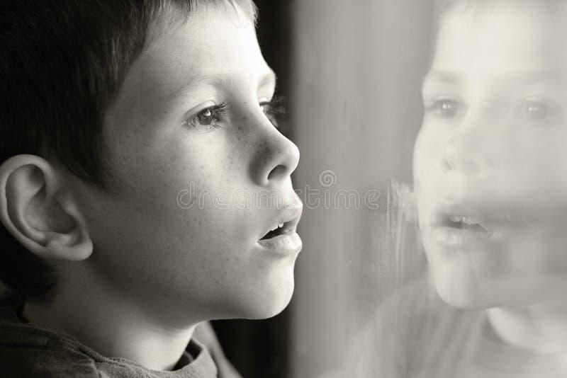 Młoda chłopiec w myśli z nadokiennym odbiciem zdjęcie royalty free