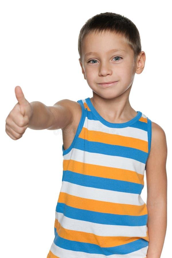 Młoda chłopiec w pasiastej koszula trzyma jego kciuk up obrazy royalty free