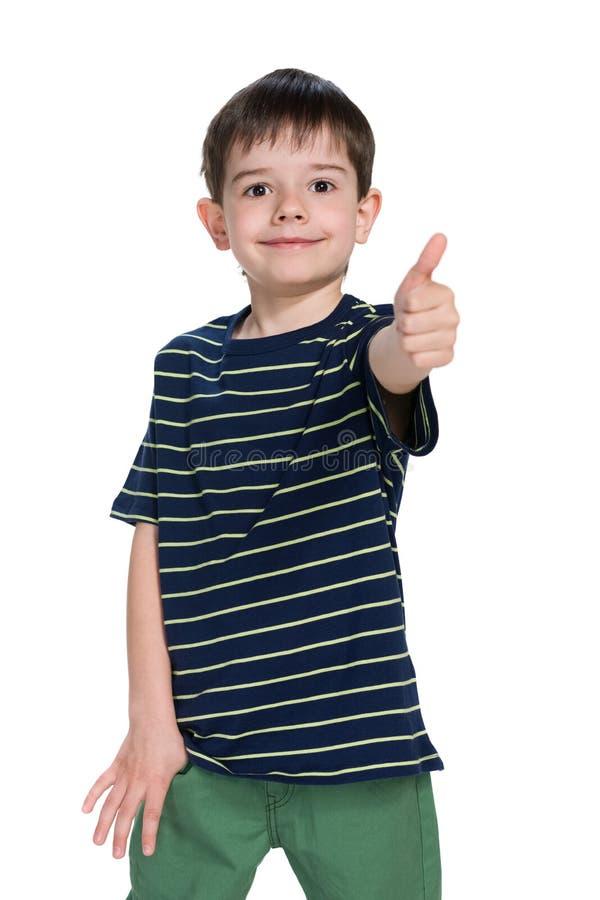Młoda chłopiec w pasiastej koszula trzyma jego kciuk up fotografia royalty free