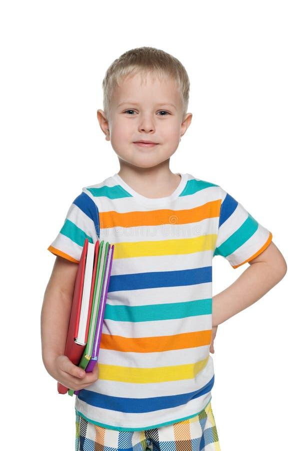 Młoda chłopiec w pasiastej koszula z książkami fotografia royalty free