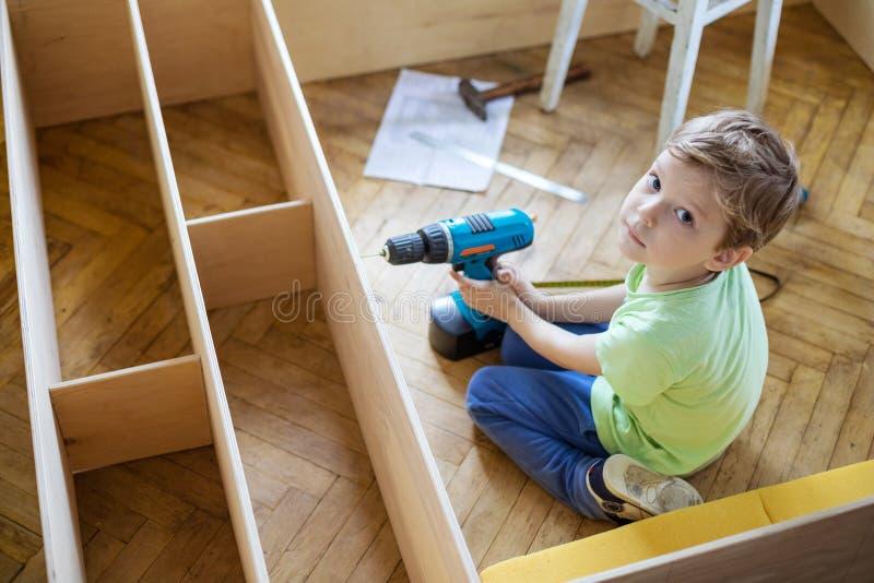 Młoda chłopiec z śrubokrętem przyglądającym up podczas gdy siedzący na podłoga zdjęcie stock