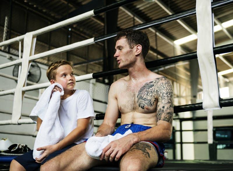 Młoda chłopiec z jego bokserskim trenerem zdjęcie stock
