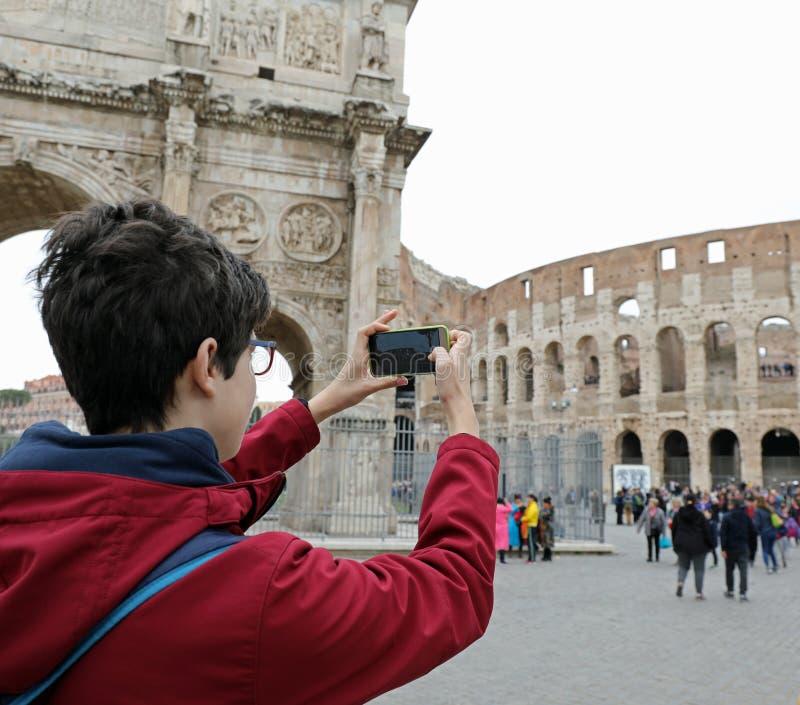 Młoda chłopiec z mądrze telefonami bierze obrazki Colosseum w Rzym obraz royalty free