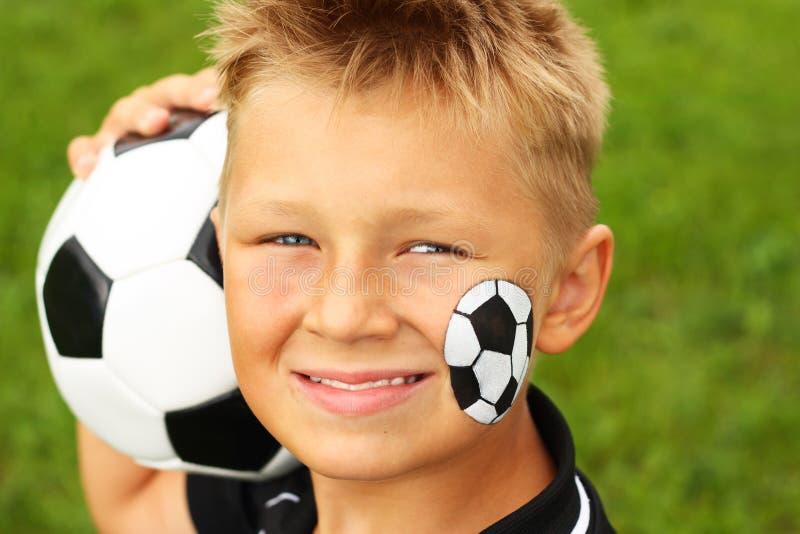 Młoda chłopiec z malującą piłki nożnej piłką i twarzą. zdjęcie royalty free