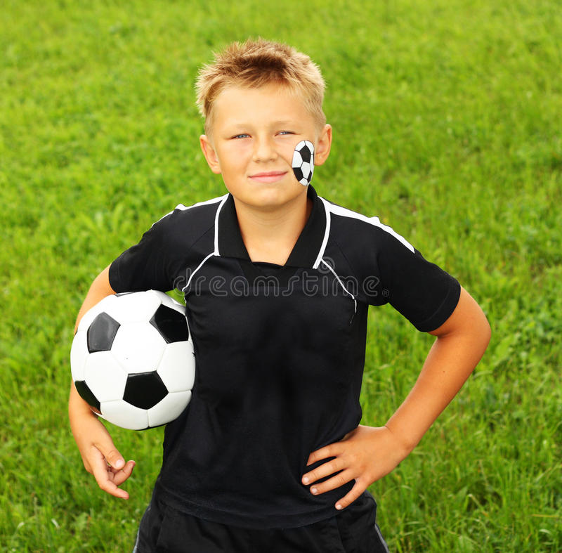 Młoda chłopiec z malującą piłki nożnej piłką i twarzą. obraz stock