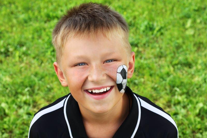 Młoda chłopiec z malującą piłki nożnej piłką i twarzą. fotografia royalty free