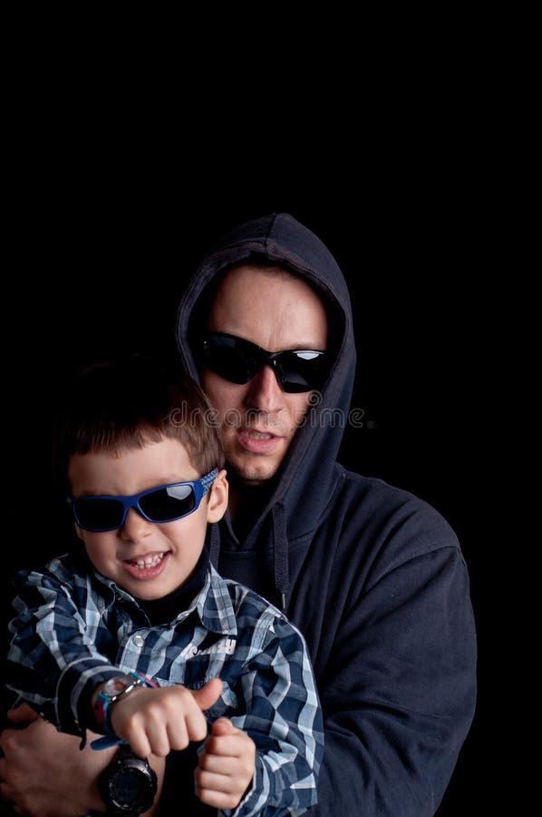 Młoda chłopiec z ojczulkiem jest ubranym okulary przeciwsłonecznych i hoodie zdjęcie stock