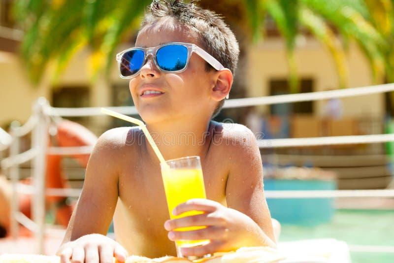Młoda chłopiec z okularami przeciwsłonecznymi na plaży i mienie soku cieszy się fotografia royalty free