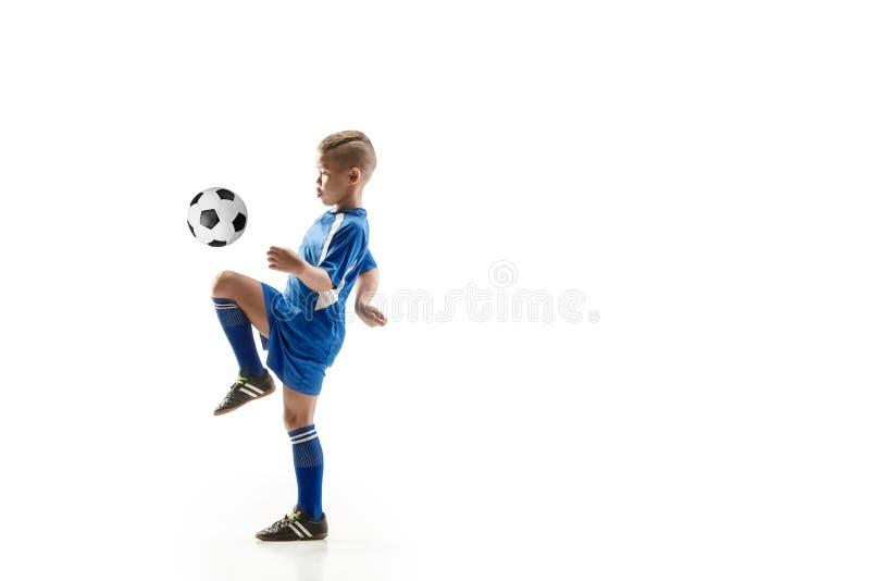 Młoda chłopiec z piłki nożnej piłką robi latającemu kopnięciu obrazy stock