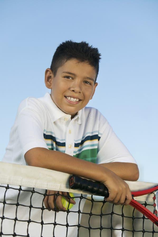 Młoda chłopiec z tenisowym kantem i balowym opierać na tenis sieci portrecie obrazy royalty free