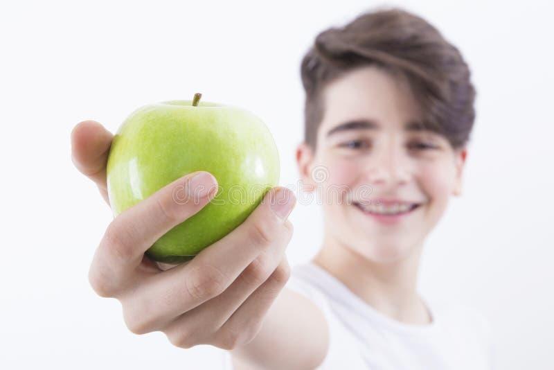 Młoda chłopiec z zielonym jabłkiem obraz royalty free