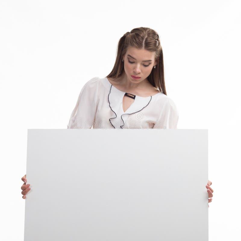 Młoda ciekawa kobieta pokazuje prezentację, wskazuje na plakacie fotografia royalty free