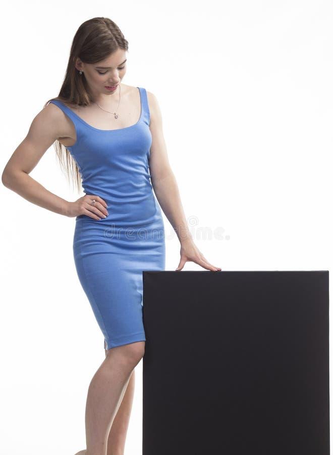 Młoda ciekawa kobieta pokazuje prezentację, wskazuje na plakacie zdjęcia stock