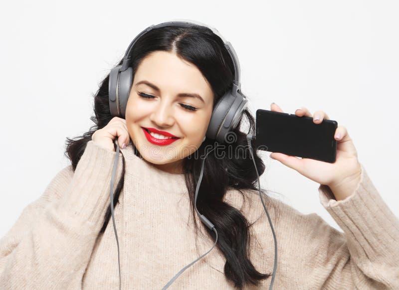 Młoda curvy brunetki kobieta słucha muzyka w hełmofonach zdjęcia royalty free