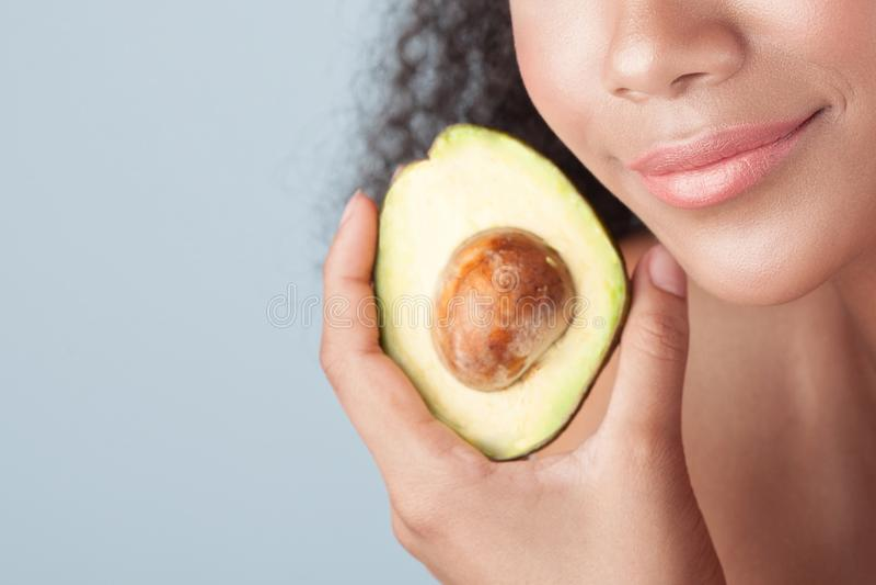 Młoda czarna dziewczyna z czystą doskonalić skórą z avocado w górę obraz royalty free